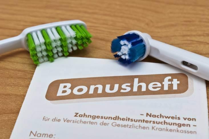 Bonusheft Zahnarzt mit Zahnbürsten liegen auf einem Tisch