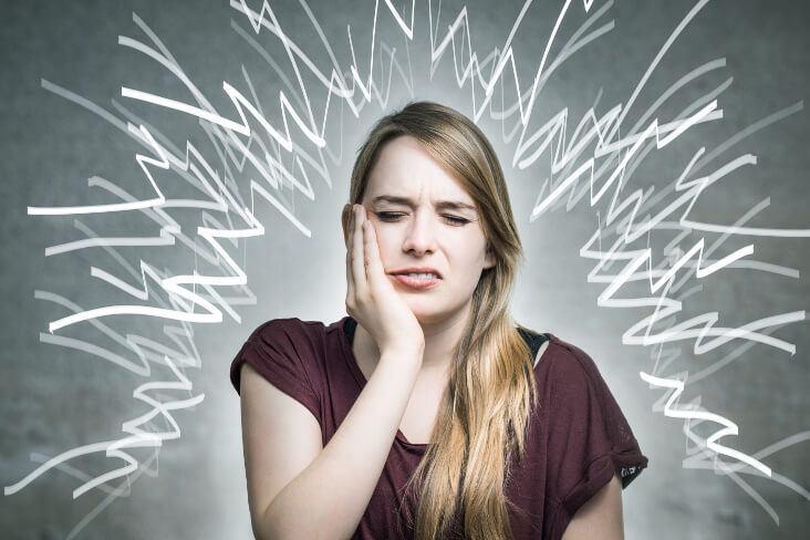 parodontose frau hält hand an die backe wegen zahnschmerzen