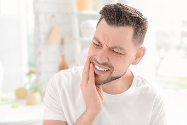 mann zahnschwerzen hand backe